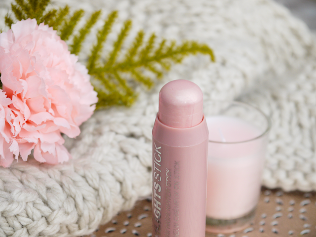 a pink highlighter stick in front of a cream woollen scarf and pink flower