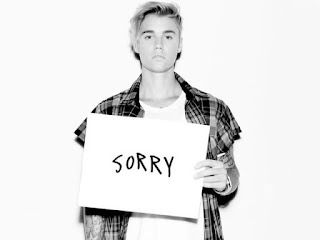 Justin Bieber holding Sorry cardboard sign