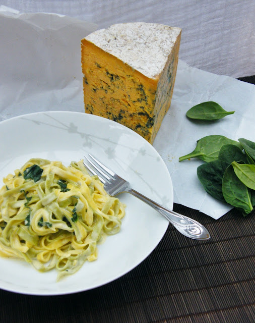 A bowl of Fettuccine with Creamy Blue Shropshire & Spinach next to a large chunk of blue shropshire cheese