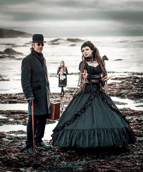 Gothic Victorian Couple with child at the beach. Black gothic clothing and costumes for men, women and kids