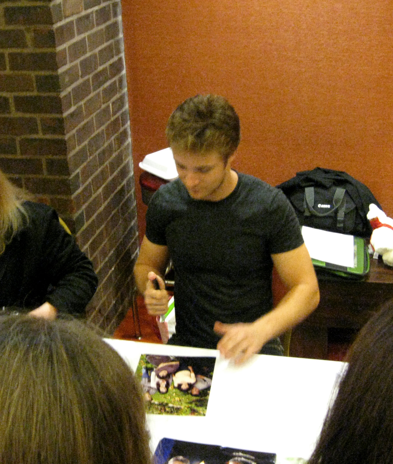 Michael Welch signing a picture from the series Joan of Arcadia