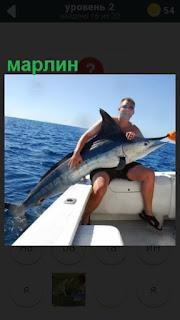 рыбак в лодке держит пойманного марлин крупного размера