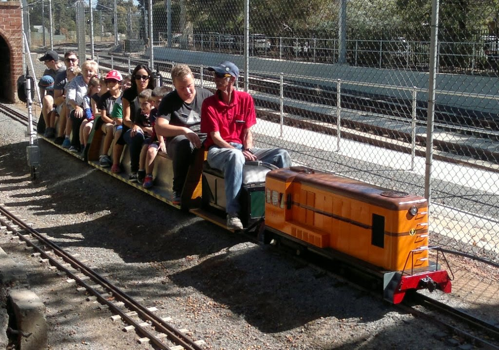 Model of a diesel locomotive pulling two carriages full of passengers.