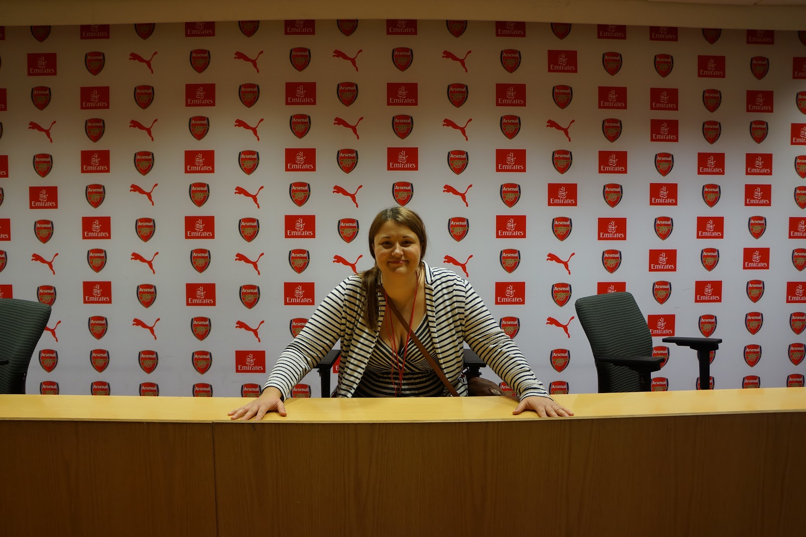 sitting at press briefing room at Arsenal Stadium Tour