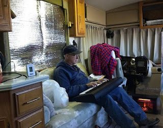 man sitting on sofa in an RV playing a small keyboard held on his lap