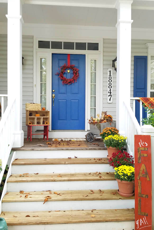 front porch with blue door and shutters, wooden and white steps, red step stool with pinecone display, fall sign