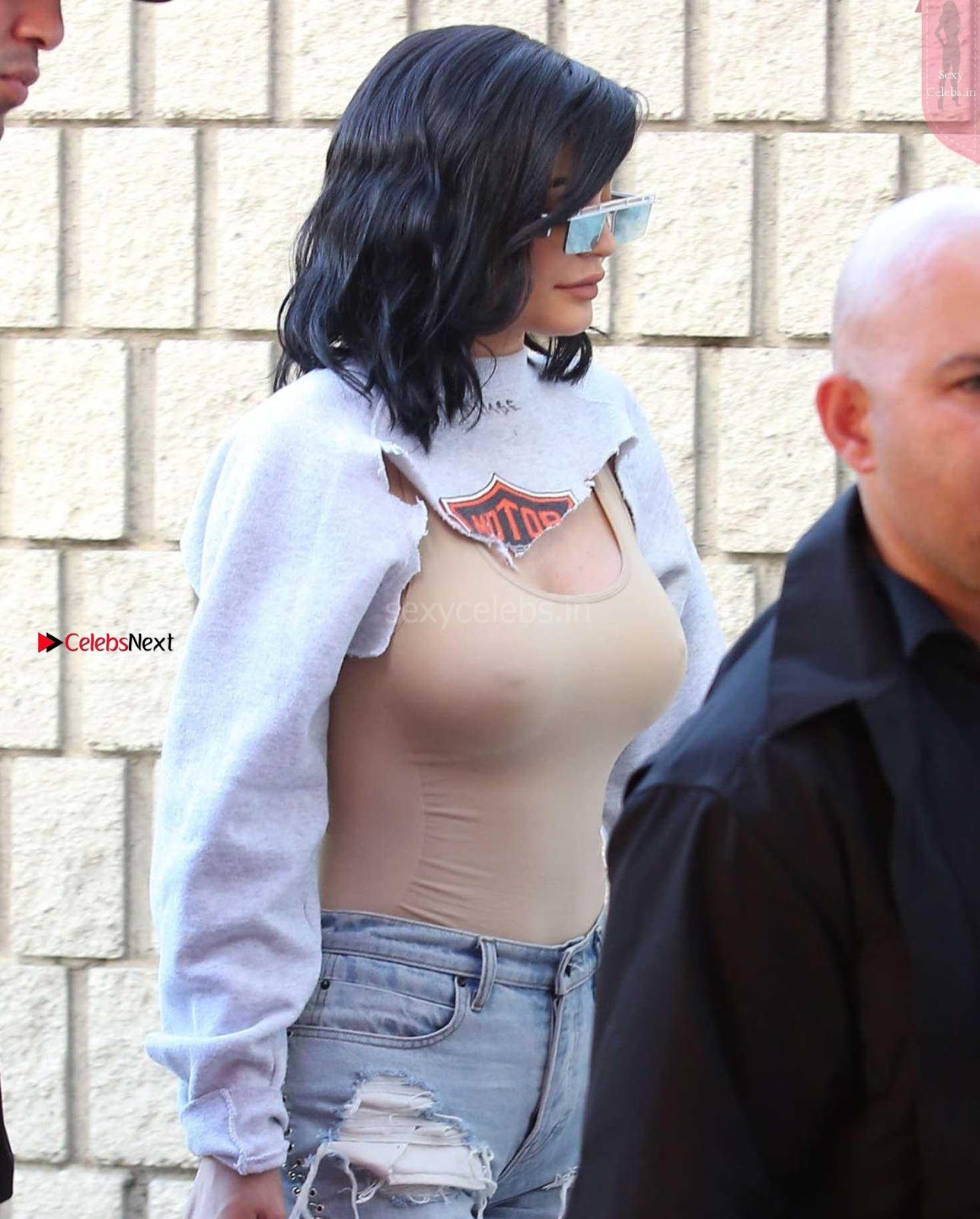 Kylie Jenner wearing a bra less nude coloured tank top exposing her huge boobs and nipples WOW