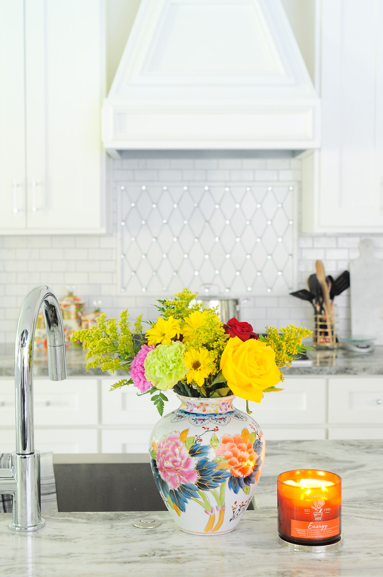 A gorgeous antique floral vase in a bright white kitchen.