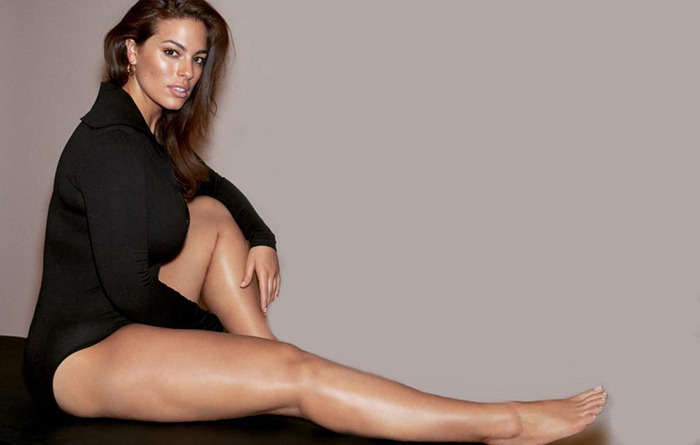 Image of plus size model ashley graham sitting in a black bodysuit