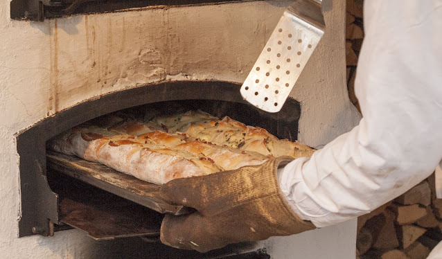 Christmas Market Food: Handbrot being pulled from a wood fired over in Berlin, Germany