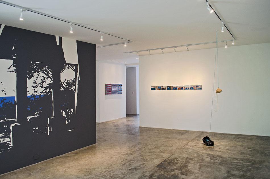 vista de sala con parte del mural con fotos y pinturas en tropical moderno