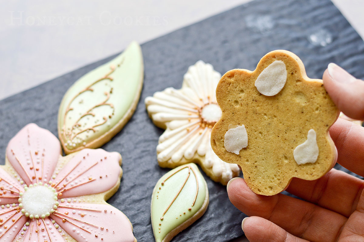 Decorated cookie removed from cushion padding showing dried dabs of royal icing, cookie and photo by Honeycat Cookies