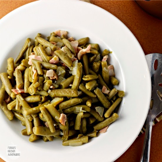 Overhead shot of country style green beans in a white bowl with a spoon on the side.