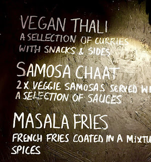 A long tall rectangular board with Masala Fries in white font on a bright background