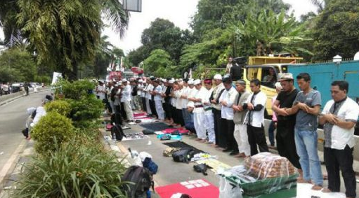 Massa dan Polisi Shalat Zuhur Berjamaah di Jalan saat Sidang Ahok Diskor
