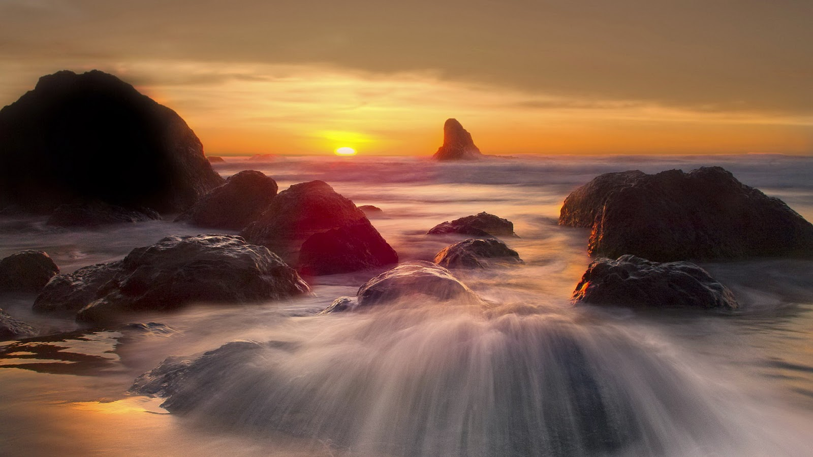 Zonsondergang met rotsen in zee 's avonds