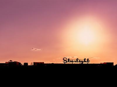 starlight sign in cursive against a cityscape and pastel sky