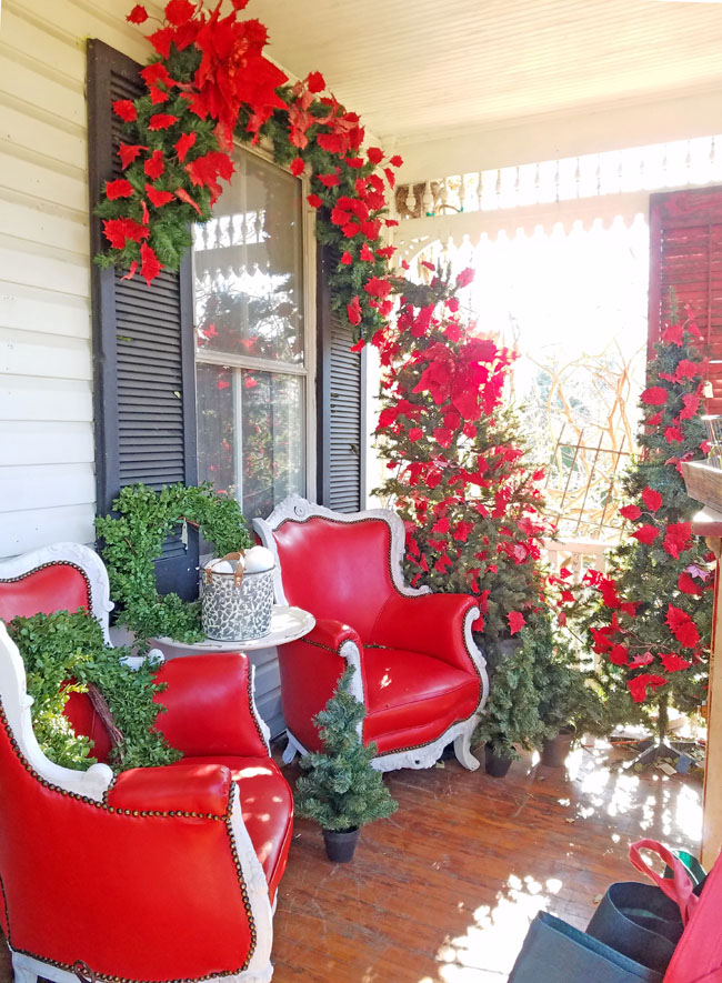 red wingback leather chairs on porch with poinsettias for Christmas decor.