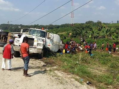 Photo of residents scooping petroleum product from fallen tanker along Calabar-Odukpani federal highway
