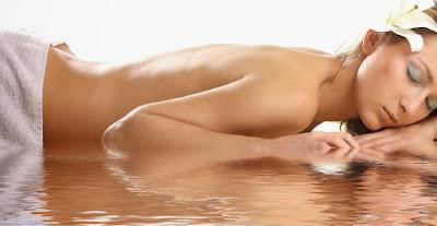 Γυναίκα γυμνή με πετσέτα και λουλούδι στο αυτί με γαλάζια σκιά ματιών ξαπλωμένη πάνω σε νερό σε σπα