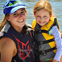 Counselor Kylie Williams and a female Keiki Camper pose for camera while sitting on a tube at Castaic Lake