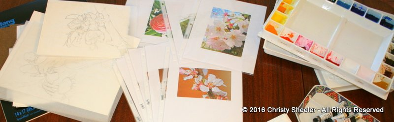 Cherry blossom sketches, photo references, and palette on the artist's work table.