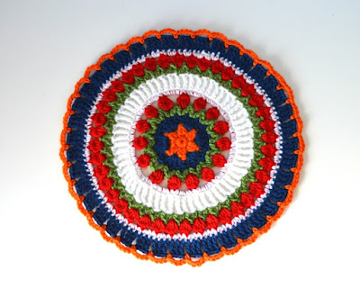 Mandala has an orange star in the centre surrounded by a blue circle. Two concentric rings of green 'leaves' and red 'tulip flowers' are separated by a wider ring of tall white stitches. After the second ring of tulips is a thin stripe of white double crochets, ending with a wider blue border with orange chain loops to finish.