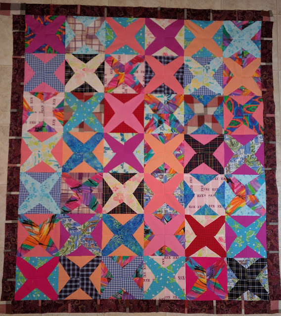 Pink, purple and blue shirts from a sister make strong Xs across this quilt.