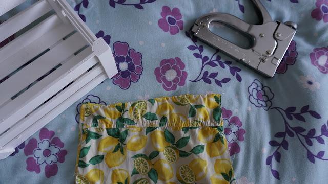 Flat lay of a white crate, staple gun and lemon print fabric