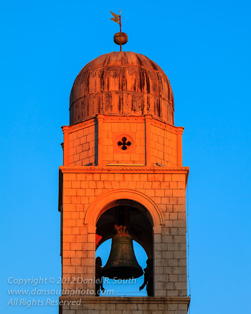 a photo of a bell tower in dubrovnik croatia in the orange glow of sunset