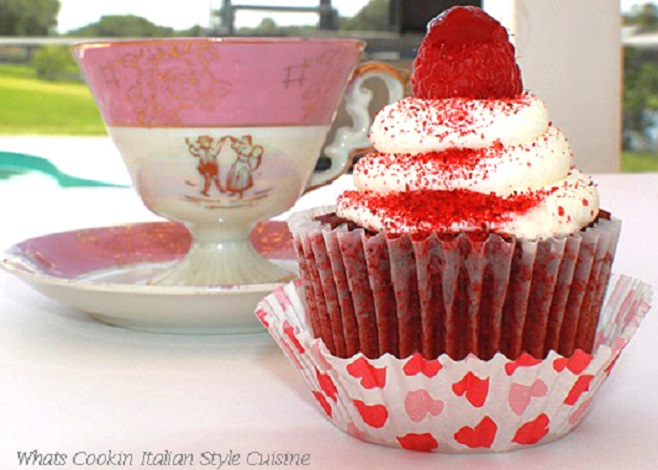 this is a photo of a raspberry red velvet cupcake with a pretty pink cup in the background. The cupcake is in a heart paper liner and covered with cream cheese frosting on top.