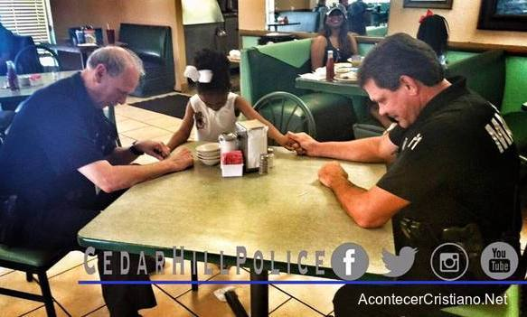 Niña orando con policías en restaurante