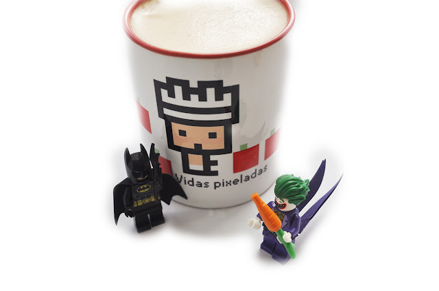 La figura de Joker de lego sostiene una zahoria delante de un lego Batman con bataran, delante de la taza de vidas pixeladas