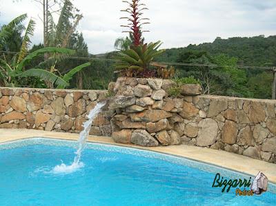 Construção de piscina com muro de pedra, a cascata de pedra com a bica d'água de madeira e o piso com caco de pedra São Tomé.