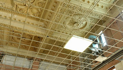 Ornate coffered ceiling with metal grid for ceiling tiles and box fluorescent lights in some of the grid spots