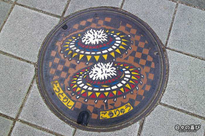 plaque d'égout de Tottori avec motif parapluie shan-shan