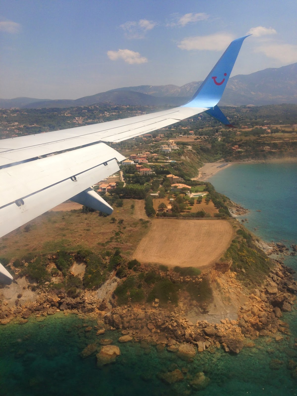 the wing of a thomson plane as it descends into kefalonia