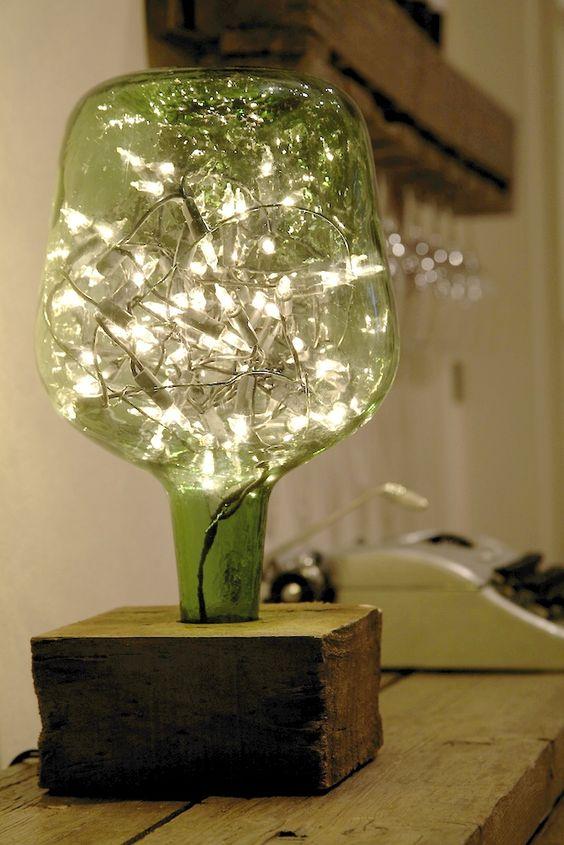 Um pedaço de madeira, um garrafão e um pisca-pisca se transformam numa luminária super original.
