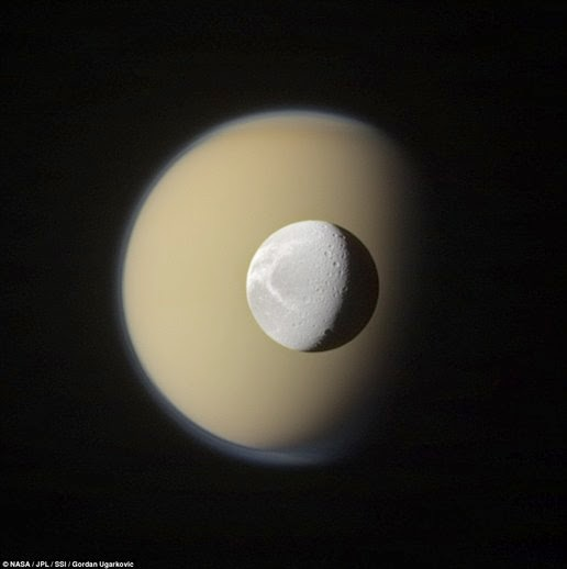 Image of Saturn's moon Titan (rear) and Dione taken by the Cassini spacecraft. When this image was taken, Titan is 3.163 million km from Cassini and Rhea is 1.611 million km
