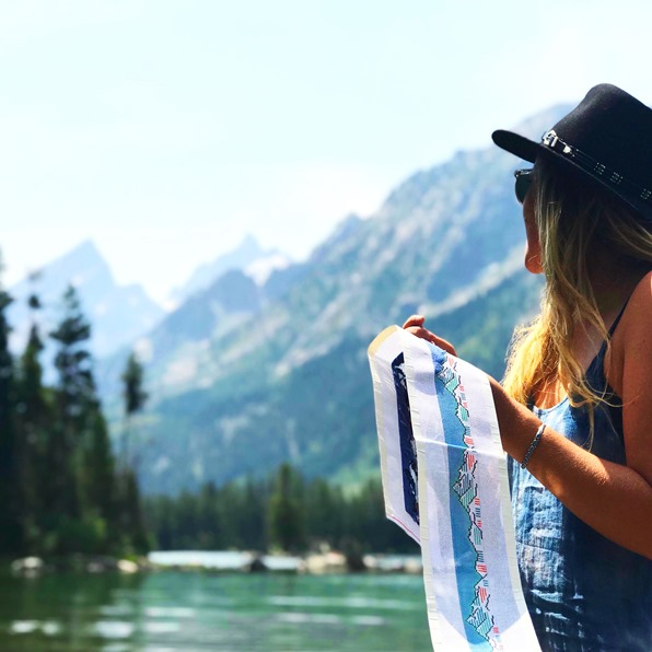 Young woman stitching a needlepoint belt canvas by a lake surrouned with mountains