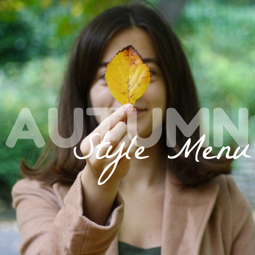 brunette holding up a yellow autumn leaf in front of her face