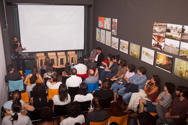 """Sala do evento """"design em diálogo"""". A imagem aparece uma sala vista do fundo para a frente - muitas pessoas de costas sentadas e na frente delas uma tela de projeção."""