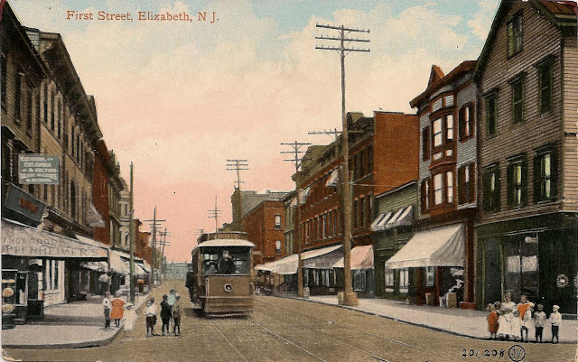 Street scene on First Street, Elizabeth, NJ. Children wait on the corners as a streetcar approaches. Oppenhimer's Fancy Goods store is also seen. The publisher, Elizabeth Novelty Co. was in exisitance between 1904 and 1916.