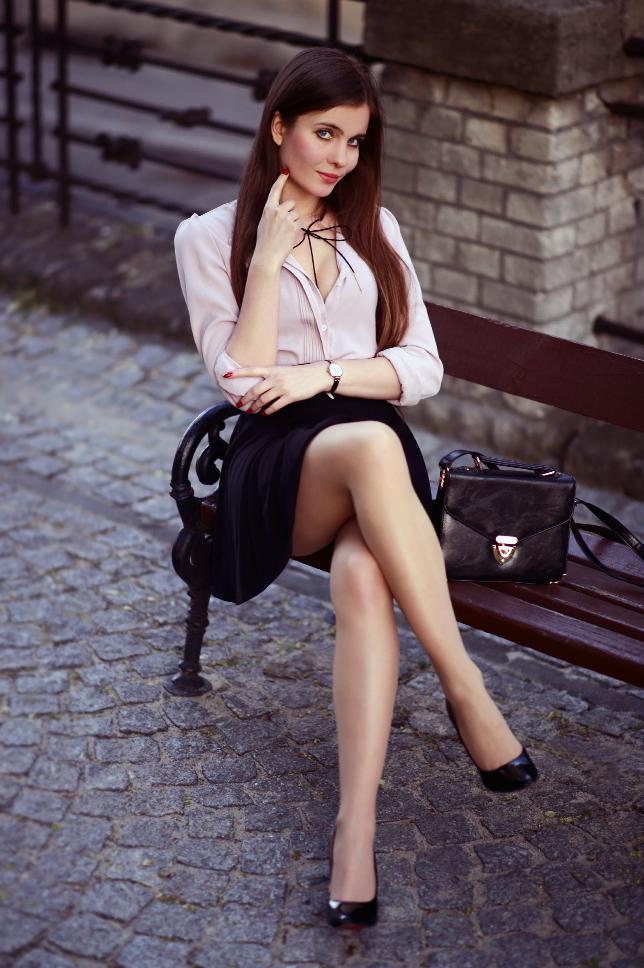 Pudrowa koszula, czarna rozkloszowana spódniczka, cieliste rajstopy i złoty naszyjnik z kokardą