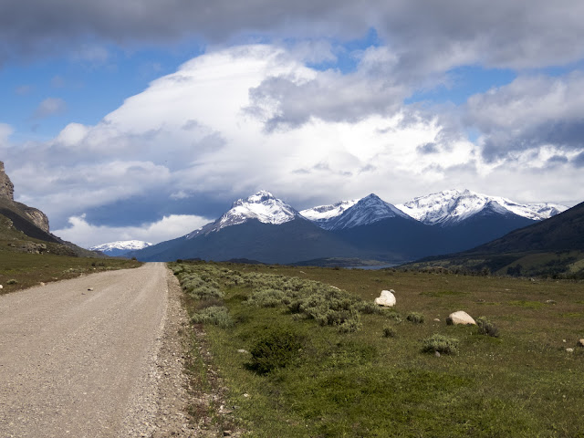 Gravel road with snowcapped mountains in the background in Patagonia Chile