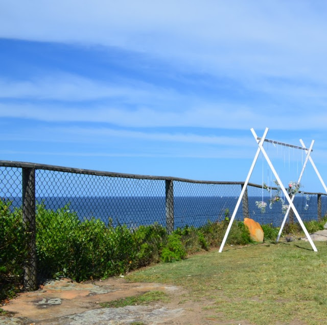 A view from the clifftop reserve overlooking the Pacific Ocean. There are light brown rocks protruding through the lawn.  A wooden-framed wire mesh fence marks the edge of the cliff. On the right hand side is a white wooden trestle used to suspend posies of flowers as wedding decorations.