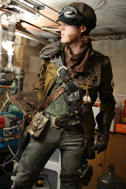 Man with mutton chops dressed in steampunk clothing. Hat, goggles, utility belt, jacket, gauntlet, satchel and trousers. Men's Steampunk Clothing.