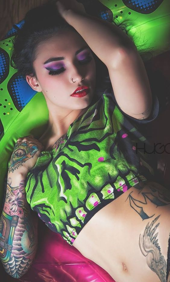 Vemos a una mujer tendida en un colchon hinchable verde, la chica lleva tatuajes en el antebrazo de una gramola, y tattoo de alas en la cadera
