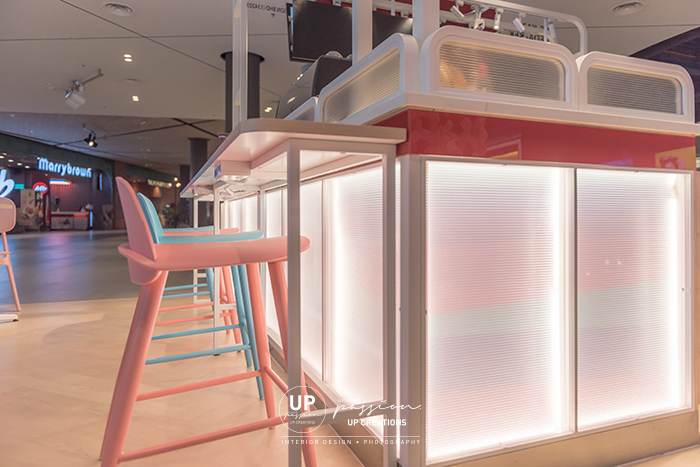 Central i city vanilla mille crepe kiosk with lighted partition in two wall poly-carbonate sheet and color stripes graphic