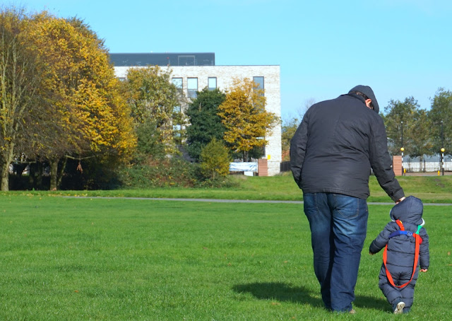 autumn photo father and toddler son standing in a park wearing coats and walking away from camera